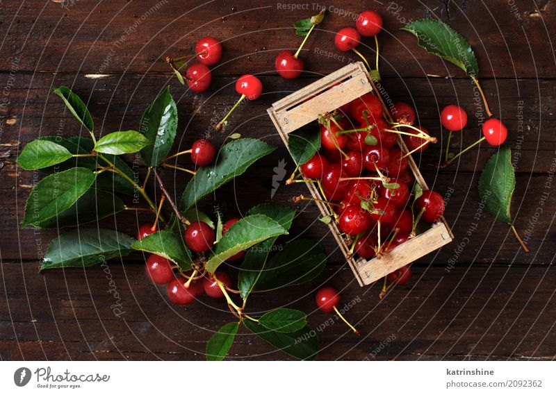 Fresh sour cherries in a box on a wooden table Summer Green Red Leaf Dark Brown Wild Fruit Table Delicious Berries Bowl Vegetarian diet Diet Vitamin