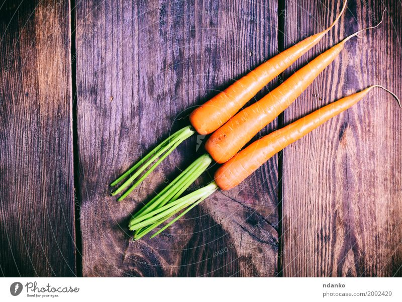 Three fresh carrots Vegetable Nutrition Eating Vegetarian diet Diet Table Nature Plant Wood Fresh Natural Green ripe Useful agriculture Organic orange Salad