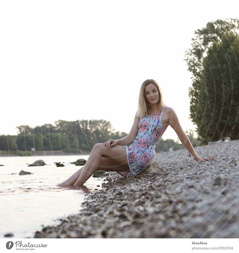 Young, slim woman in a summer dress sits on the banks of the Rhine with her feet in the water Joy pretty Life Well-being Young woman Youth (Young adults) Body