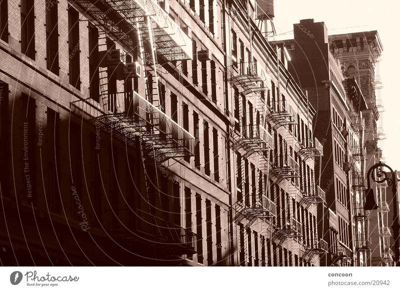 South of Houston (SoHo) Soho New York City Fire ladder North America USA cast iron turn of the century old houses Sun Sepia