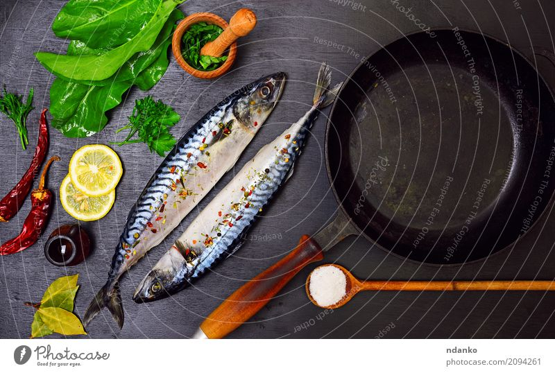 Two mackerels in spices Seafood Herbs and spices Nutrition Lunch Dinner Diet Pan Spoon Ocean Table Restaurant Gastronomy Nature Animal Wood Fresh Natural Green
