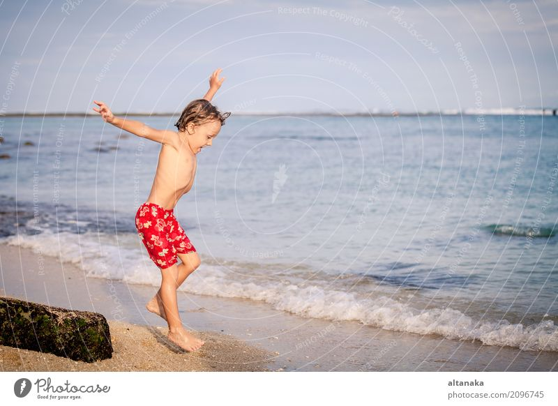 Happy little boy jumping on the beach Lifestyle Joy Relaxation Leisure and hobbies Playing Vacation & Travel Trip Adventure Freedom Summer Sun Beach Ocean Child
