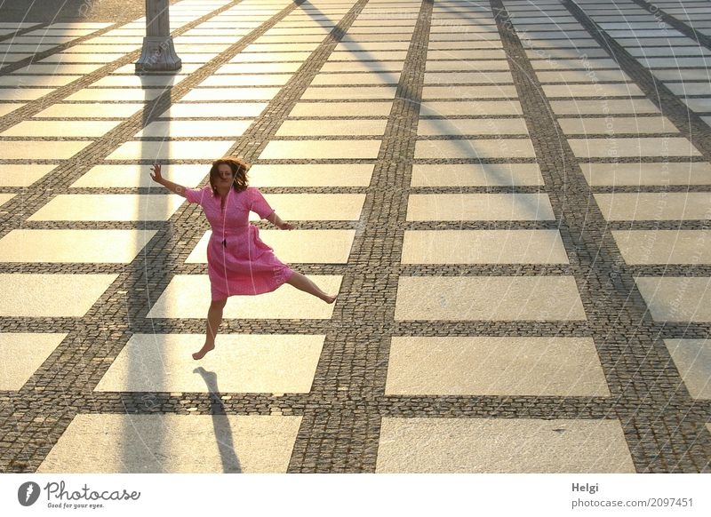 Woman with long brunette hair and pink dress jumping barefoot on a large paved square against the light Human being Feminine Adults 1 45 - 60 years Chemnitz