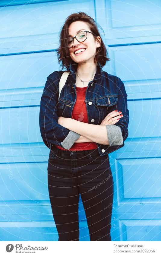 Young woman in front of blue wall Feminine Youth (Young adults) Woman Adults 1 Human being 18 - 30 years 30 - 45 years Joy luck Good mood Positive Jeans jacket