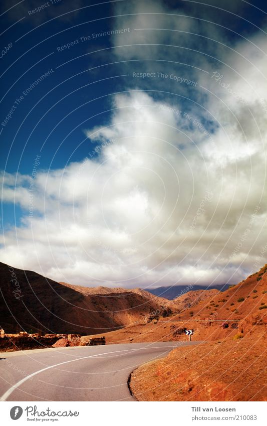 Road through Red Environment Nature Sky Clouds Summer Weather Rock Traffic infrastructure Street Blue Gray White Signs and labeling Morocco Mountain Atlas