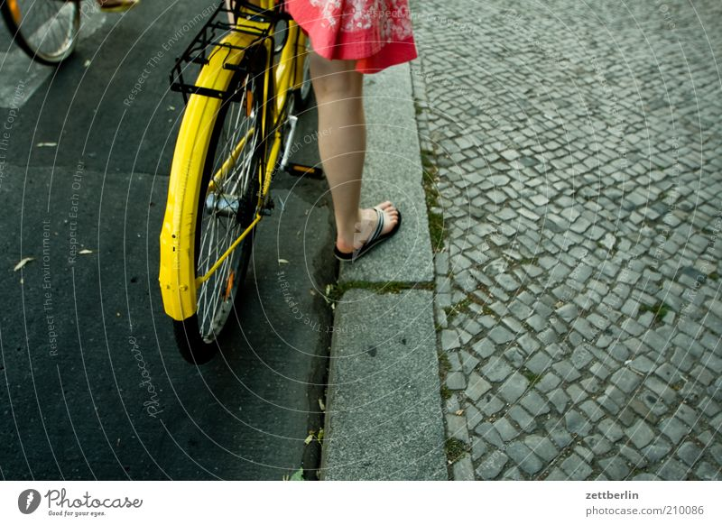 Human being Woman Summer Adults Legs Feet Bicycle Wait Transport Stand Driving Dress Sidewalk Skirt Cobblestones Wheel