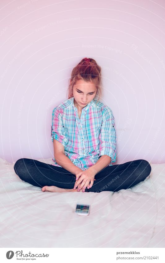 Young girl looking at mobile phone while sitting on bed Human being Child Youth (Young adults) Girl Lifestyle Modern 13 - 18 years Technology Telephone