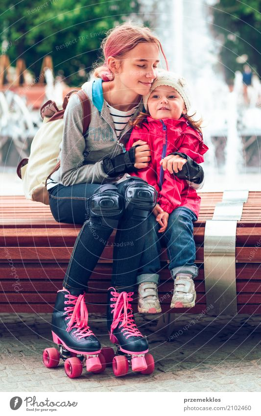 Young girl hugging her little sister while sitting on bench Lifestyle Child Toddler Girl Sister Family & Relations 2 Human being 1 - 3 years 13 - 18 years