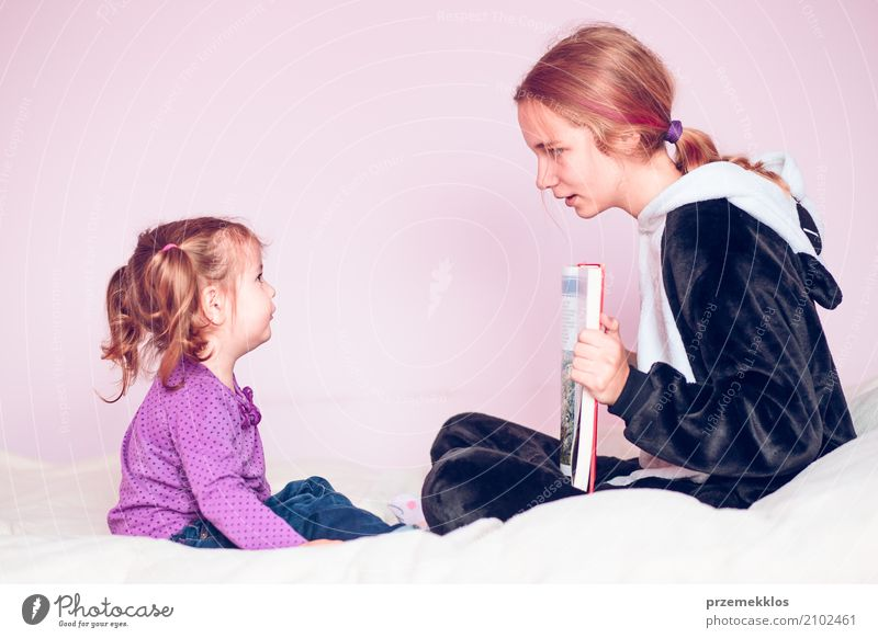 Girl showing the pictures in a book her younger sister Lifestyle Bed Child To talk Toddler Sister 2 Human being 1 - 3 years 13 - 18 years Youth (Young adults)