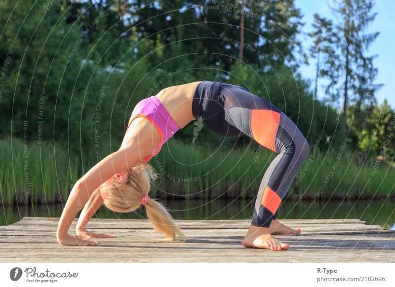 A sporty woman doing yoga and stretching exercises Lifestyle Wellness Harmonious Sports Yoga Human being Woman Adults Nature Park Fashion Blonde Fitness
