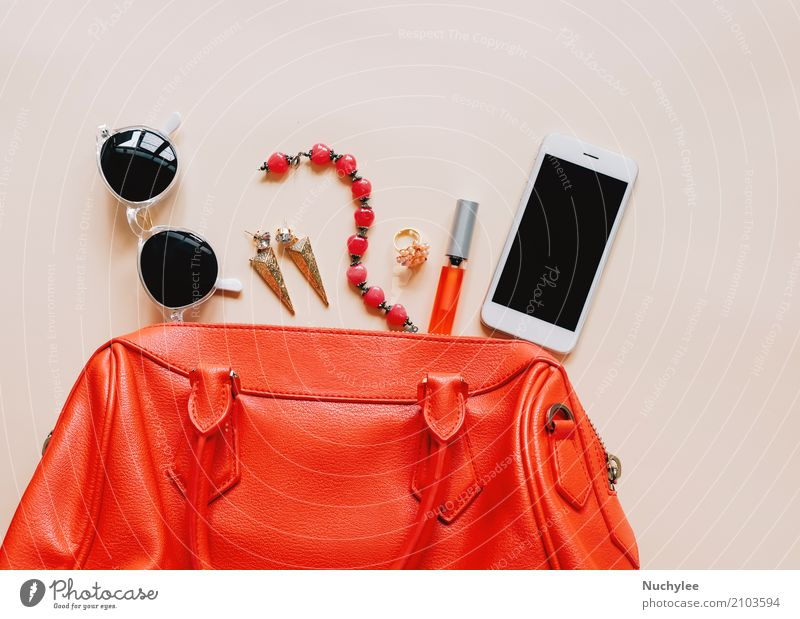 Flat lay of red leather woman bag open out with cosmetics Elegant Style Design Beautiful Make-up Lipstick Vacation & Travel Telephone PDA Technology Feminine