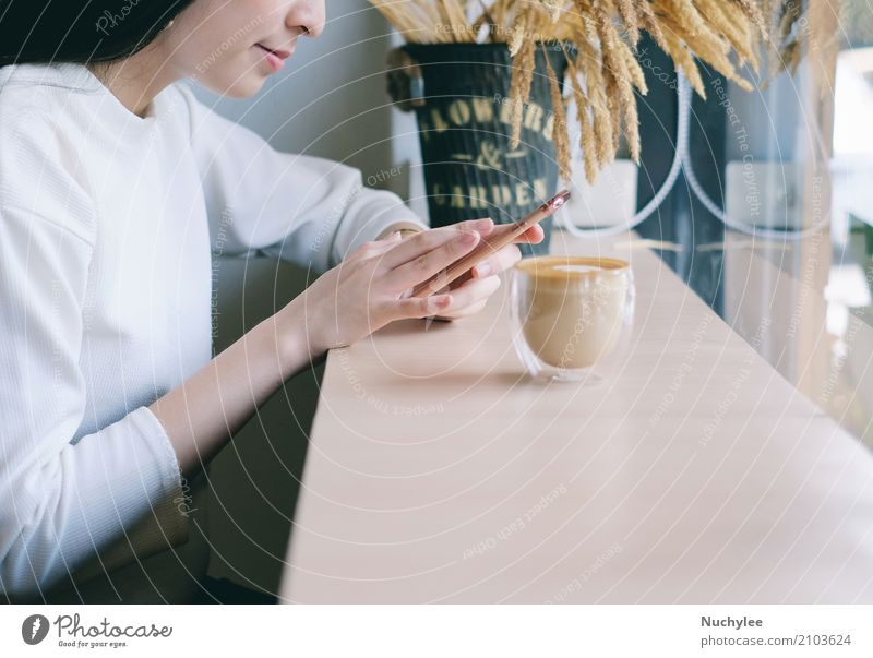 Young woman using smartphone in the cafe Beverage Coffee Lifestyle Style Happy Relaxation Leisure and hobbies Telephone Cellphone PDA Technology Internet Woman