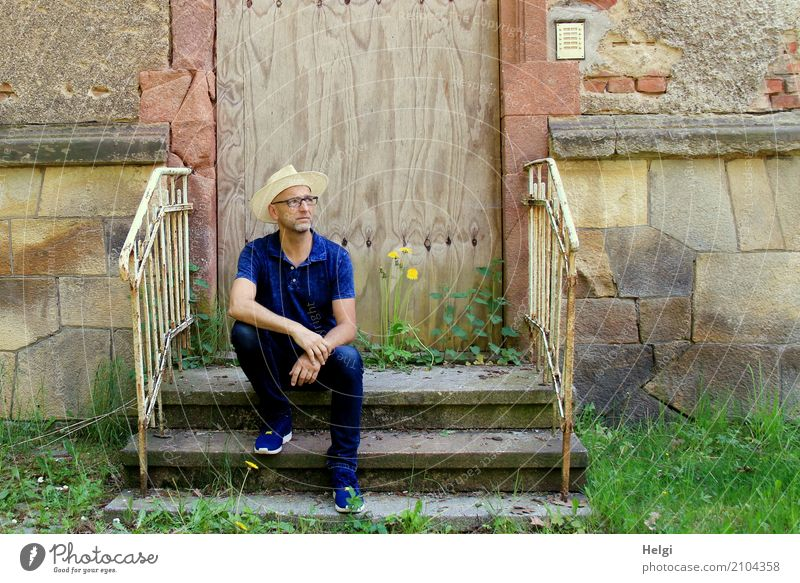 Man with beard, glasses and sun hat sits casually on a staircase in front of a dilapidated building Human being Masculine Adults Male senior Senior citizen 1