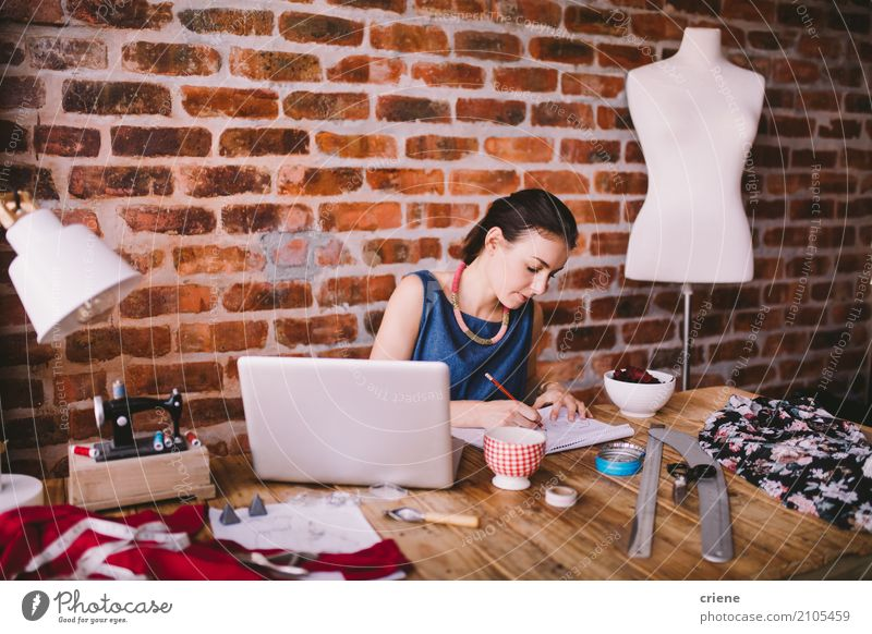 Young female fashion designer working at desk in office Human being Youth (Young adults) Young woman Adults Feminine Business Work and employment Office Modern Technology Sit Paper Reading Concentrate Desk Home