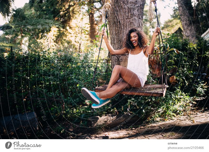 African Woman sitting on swing in the garden in summer Human being Youth (Young adults) Young woman Summer Sun Tree Joy 18 - 30 years Adults Lifestyle Feminine