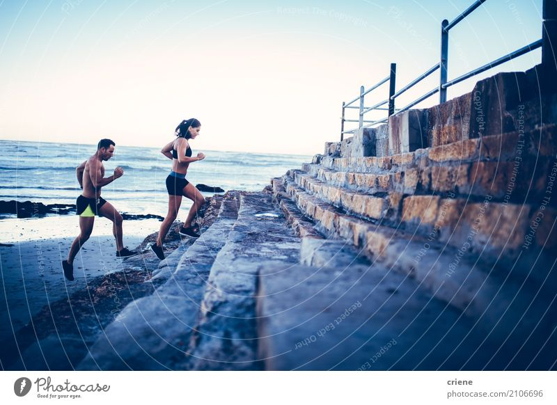 Fit young adult couple running at beach together Lifestyle Joy Athletic Fitness Leisure and hobbies Beach Ocean Sports Human being Woman Adults Man Couple 2
