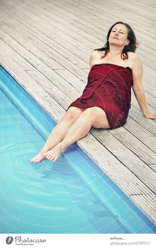 Mature brunette woman sunbathing by the pool with her feet in the water wrapped in a bath towel Lifestyle Well-being Contentment Relaxation Calm