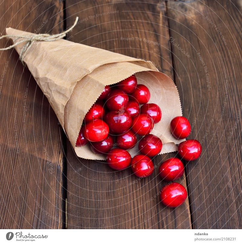 Ripe red cherry in a paper bag Fruit Dessert Eating Vegetarian diet Juice Summer Table Nature Paper Wood Fresh Natural Above Retro Juicy Red background Berries