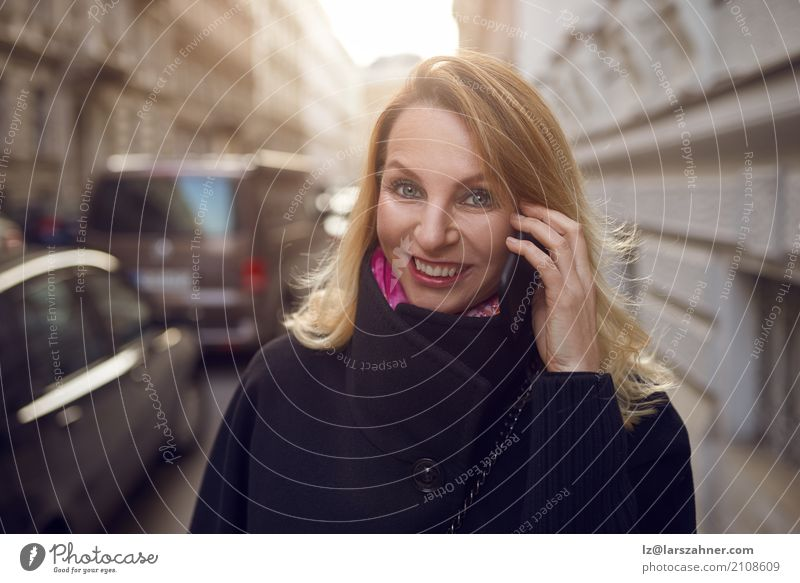 Pretty vivacious woman chatting on a mobile Happy Face Success Business Telephone Technology Woman Adults 1 Human being 30 - 45 years Street Smiling