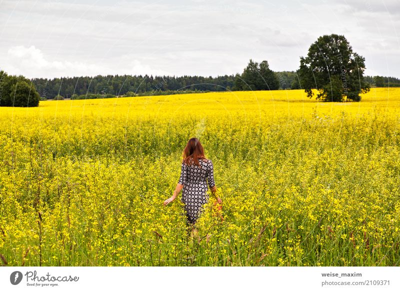 Young beautiful woman in a flowering rapeseed field Human being Woman Nature Vacation & Travel Youth (Young adults) Plant Young woman Summer Colour Beautiful