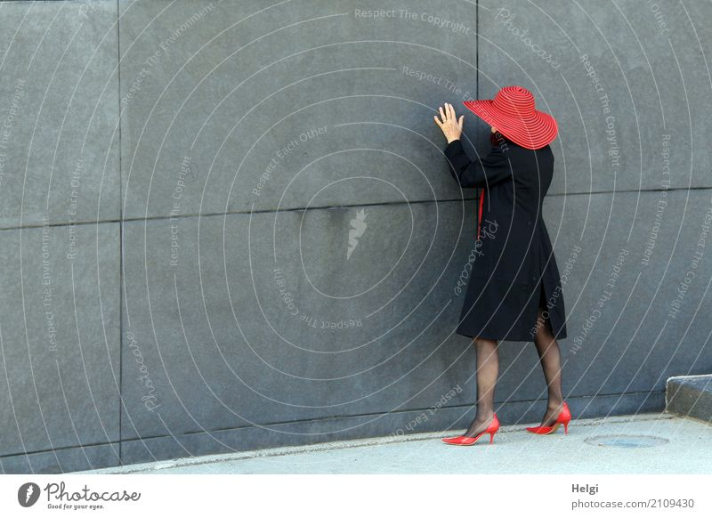rear view of an elegantly dressed lady with black coat, red hat and red pumps in front of a grey wall Human being Feminine Woman Adults Female senior