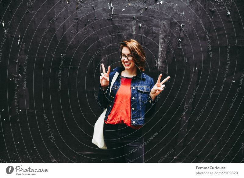 Young attractive brunette woman with glasses in front of black wall shows Victory sign with her hands Feminine Young woman Youth (Young adults) Woman Adults 1