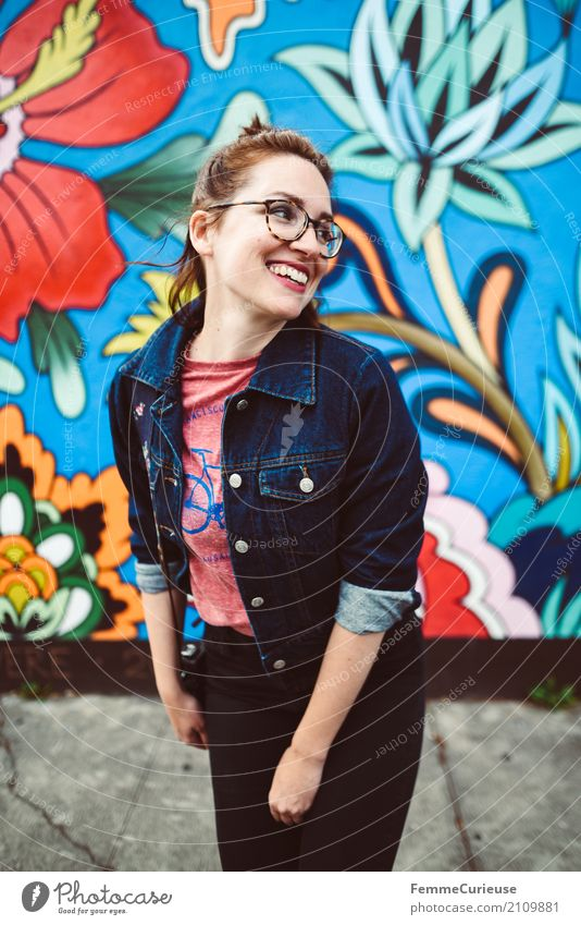 Young attractive woman with glasses and jeans jacket smiling in front of colorful wall Feminine Young woman Youth (Young adults) Woman Adults 1 Human being