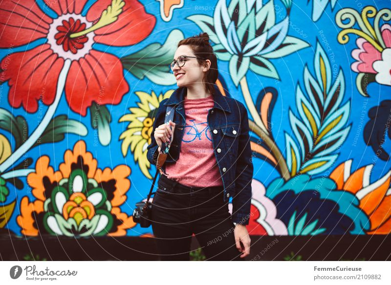 Young attractive woman with glasses, jeans jacket and reflex camera in front of colorful wall Feminine Young woman Youth (Young adults) Woman Adults 1