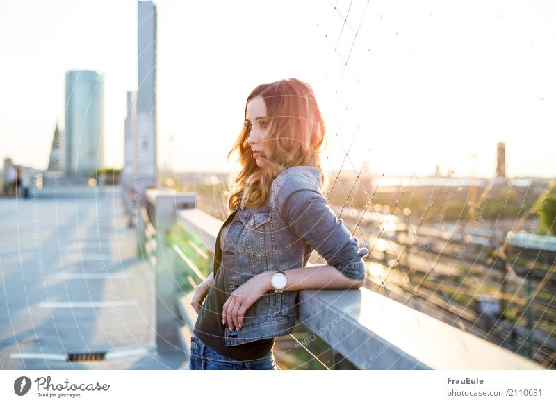 above the roofs II Feminine Young woman Youth (Young adults) Woman Adults 1 Human being 18 - 30 years Town Skyline Parking garage Roof Jeans Jeans jacket Clock