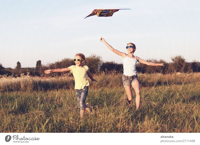 Happy children playing on the field at the day time. Concept of friendly siblings of family. Lifestyle Joy Beautiful Leisure and hobbies Playing