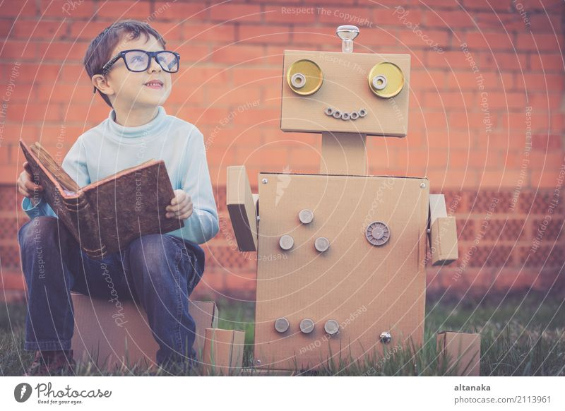 One little boy reading to robot from cardboard boxes outdoors Human being Child Nature Man Summer Beautiful Relaxation Joy Adults Lifestyle Grass Boy (child)