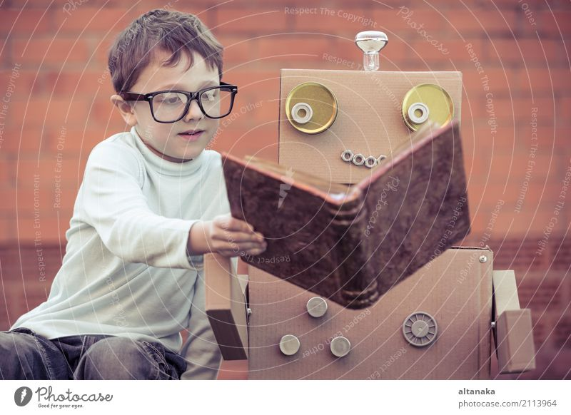 One little boy reading to robot from cardboard boxes outdoors. Concept of science and education. Lifestyle Joy Happy Beautiful Relaxation Leisure and hobbies