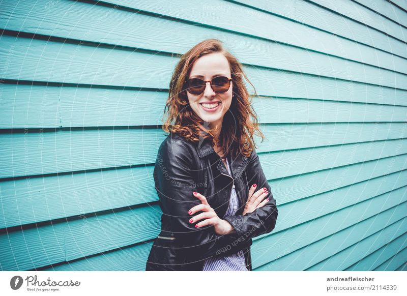 Laughing young woman with sunglasses in front of turquoise wooden facade Lifestyle Vacation & Travel Tourism Trip Far-off places Freedom Sightseeing City trip