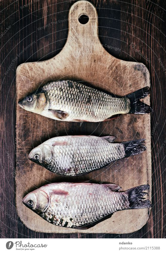 Three fresh river fish carp Fish Eating Diet River Wood Retro Brown crucian food three kitchen board cook Live vintage Edible scales whole Tasty Top cooking Raw