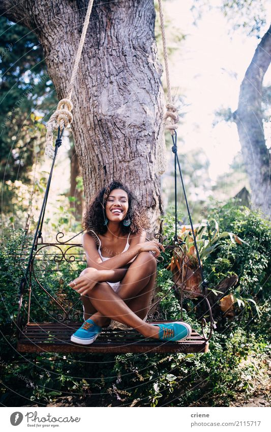 Happy African young woman sitting on swing under tree in garden Lifestyle Well-being Summer Sun Human being Feminine Young woman Youth (Young adults) 1 Nature