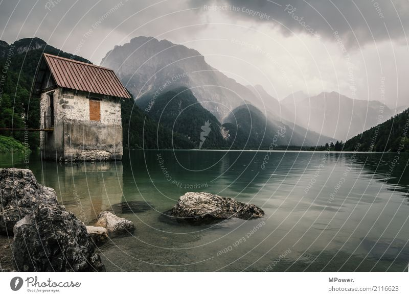 the lake of Ribles Environment Nature Landscape Storm clouds Summer Bad weather Wind Rain Alps Mountain Peak Lake Dark Moody Mountain lake Hut Italy