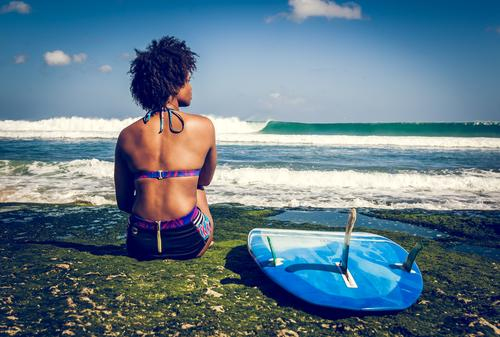 Surfer girl on green coral reef Young woman Youth (Young adults) 1 Human being 18 - 30 years Adults Vacation & Travel Competition Power Break Surfboard Sit Afro