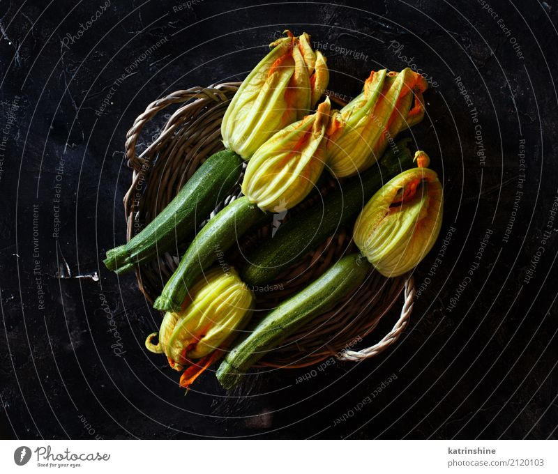 Zucchini with flowers on a dark background top view Food Vegetable Nutrition Vegetarian diet Table Group Flower Dark Fresh Yellow Green Harvest healthy