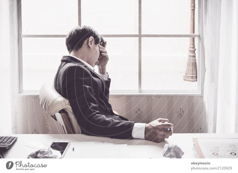 A stressed out business man holds his head Man Adults Boy (child) Business Success Poverty Shopping Money Stress Economy Home Suit Bank note Sell