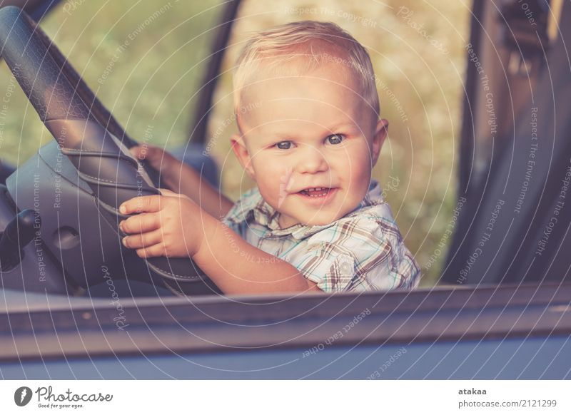 One little boy sitting in the car and look out from the car window at the day time. Concept of happy trip. Lifestyle Joy Happy Beautiful Leisure and hobbies
