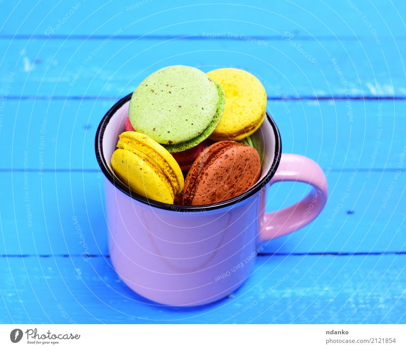 Almond biscuit macaron in a mug Dessert Candy Cup Mug Table Gastronomy Wood Bright Delicious Above Blue Brown Yellow Green Pink Tradition colorful background