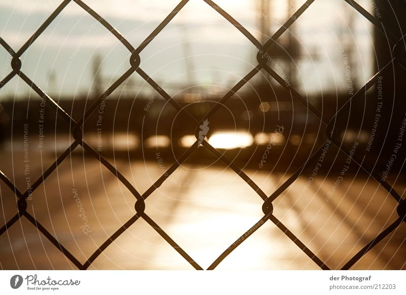 Behind borders Harbour Fence Barrier Colour photo Exterior shot Close-up Deserted Twilight Sunlight Blur Wire netting fence Brownish Border Day