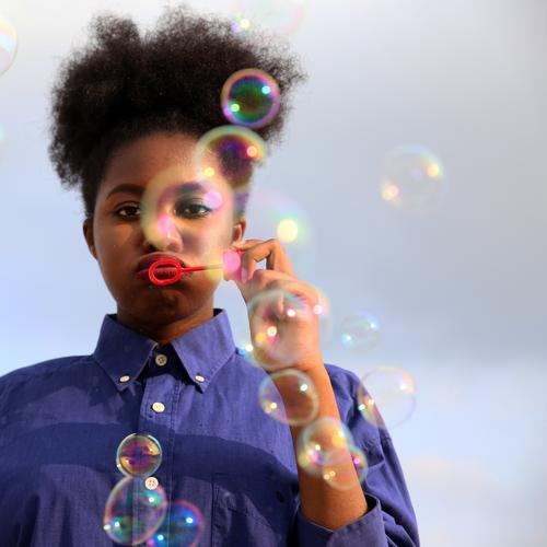 Life elixir bubblefun Feminine Woman Adults 1 Human being Sky Clouds Beautiful weather Shirt Hair and hairstyles Black-haired Curl Afro Soap bubble Observe