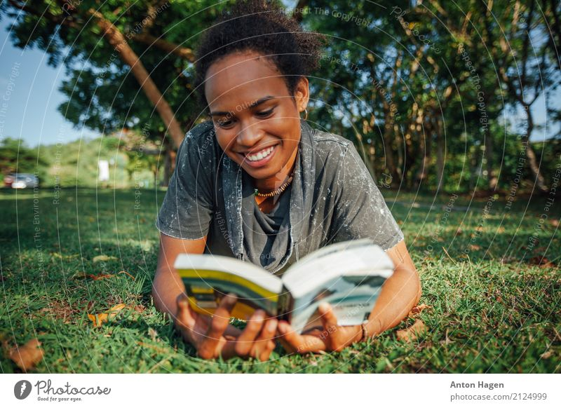 Young woman reading book in the park Human being Youth (Young adults) Summer Green Tree 18 - 30 years Adults Grass Laughter Park Lie Smiling Blossoming Study