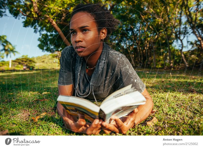 Young afro american woman reading book lying on the green lawn Lifestyle Feminine Young woman Youth (Young adults) 1 Human being 18 - 30 years Adults