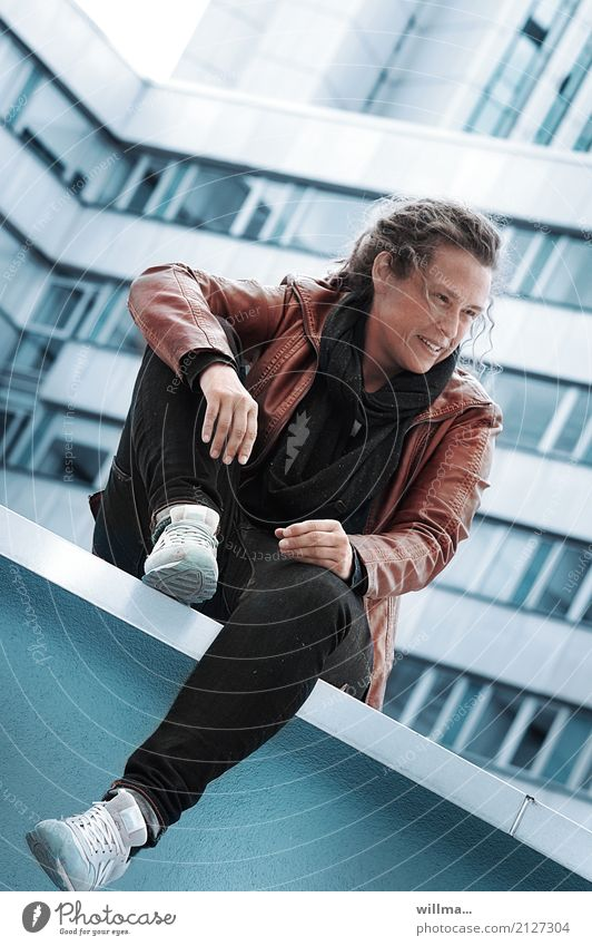 young woman in leather jacket sitting casually on a wall in the city Lifestyle Human being Young woman Youth (Young adults) Woman Adults High-rise