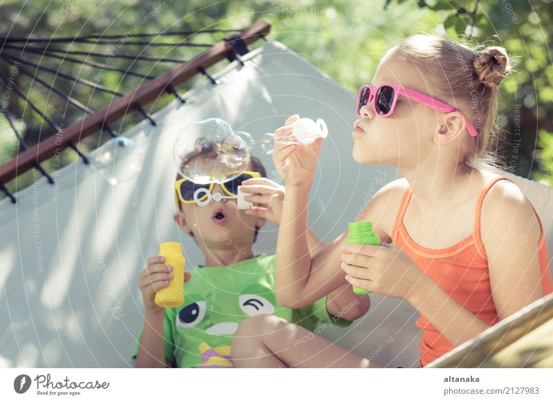 Two happy children lie on a hammock and play with soap bubbles. Human being Child Nature Summer Beautiful Green Sun Relaxation Joy Lifestyle Funny Love Grass
