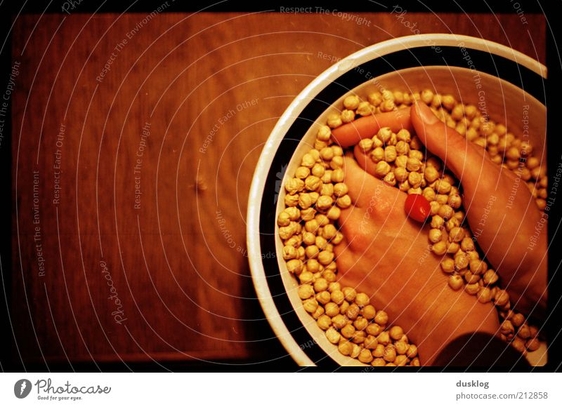 chickpeas Food Nutrition Bowl Skin Hand Fingers Chickpeas Table Wood Emotions Scrabble about Yellow Brown Red Point Colour photo Interior shot Copy Space left