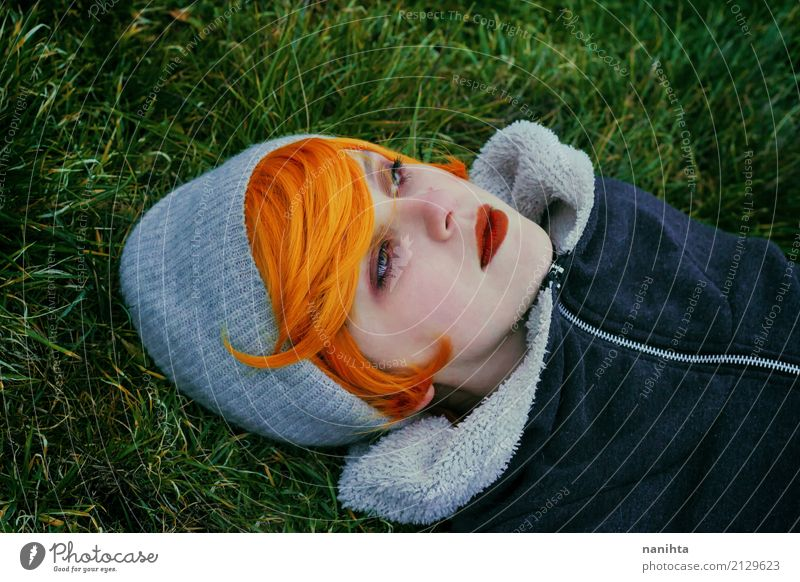 Young redhead woman lying on a field of grass and looking away Human being Nature Youth (Young adults) Young woman Beautiful Green Loneliness 18 - 30 years Face