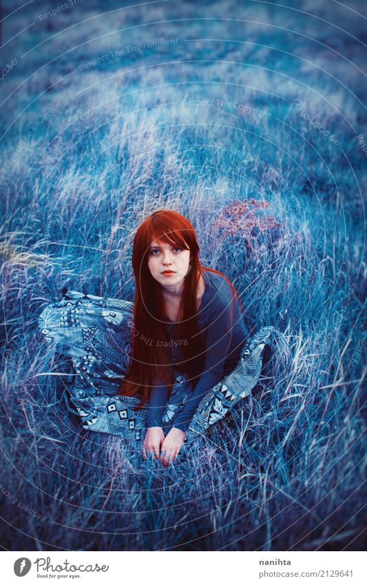 Young redhead woman sitting on a field of blue grass Human being Nature Youth (Young adults) Blue Young woman Beautiful Red Loneliness Calm 18 - 30 years Adults